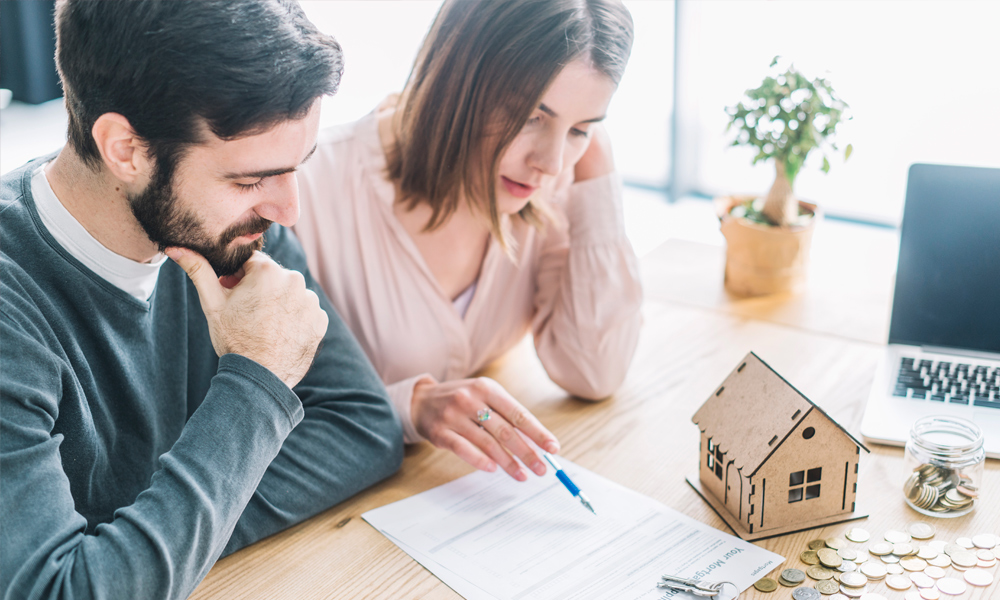 Couple Reviewing Checklist For Mortgages